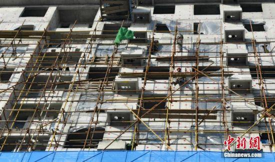 """2021年首日,当清晨第一缕阳光照射在拥有近300座建筑工地,10万多工人的雄安新区,这个全球最大的施工现场又开始了一天的""""忙碌""""。图为容东片区G组团安置房及配套设施工程G2标段三工区施工现场。 中新社记者 韩冰 摄"""