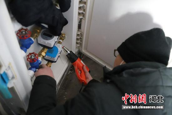 维修人员正在用电吹风给水管解冻。 王思棋 摄