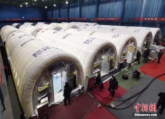 """1月8日晚,河北石家庄,工作人员在""""火眼""""实验室建设现场忙碌。 中新社记者 翟羽佳 摄"""