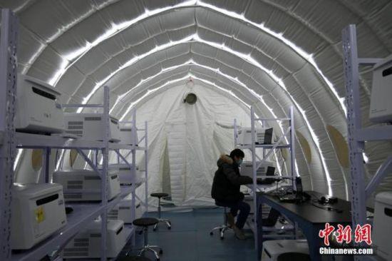 """1月8日晚,河北石家庄,工作人员在""""火眼""""实验室建设现场忙碌。中新社记者 翟羽佳 摄"""