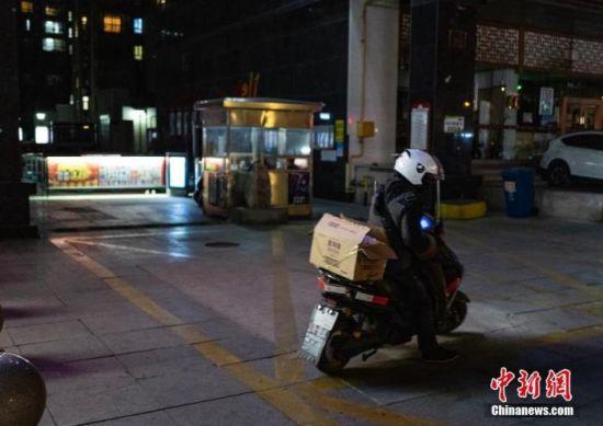 1月9日,河北省石家庄市的一名快递送货员为一处小区的居民派送生活必需品后驾车离开。 中新社记者 侯宇 摄