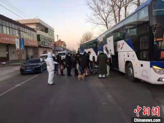 图为小果庄村村民被转移隔离时,警员维持秩序。 张月礼 摄