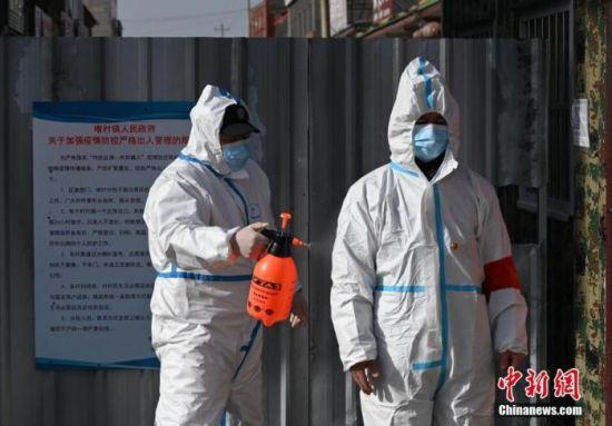 图为警员为从小果庄村出来的防疫工作人员消毒。 中新社记者 翟羽佳 摄
