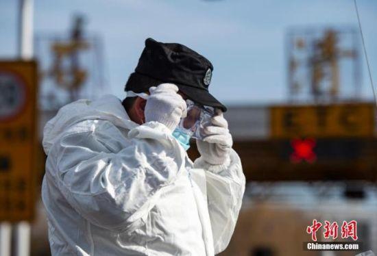 """1月10日,首个""""中国人民警察节""""当天,河北省石家庄市,警察在高速公路通向市区的石清路下站口执勤,坚守抗疫一线。 中新社记者 侯宇 摄"""