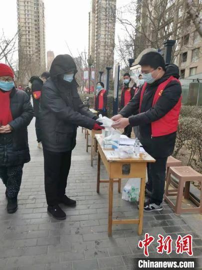 图为社区志愿者为社区居民代购药品。 李娅丽 摄
