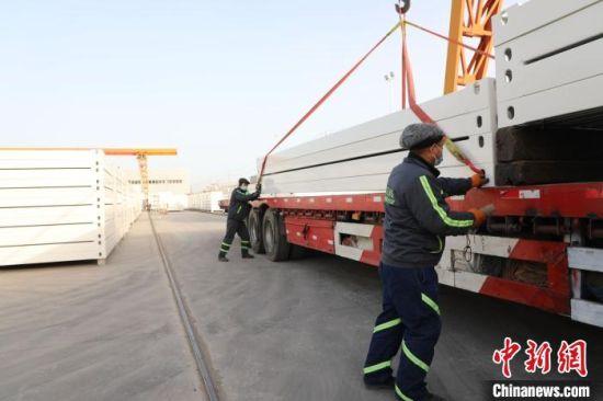 图为唐山芦台经济开发区的工人正在将集成房屋装车运往石家庄抗疫一线。 白云水 摄