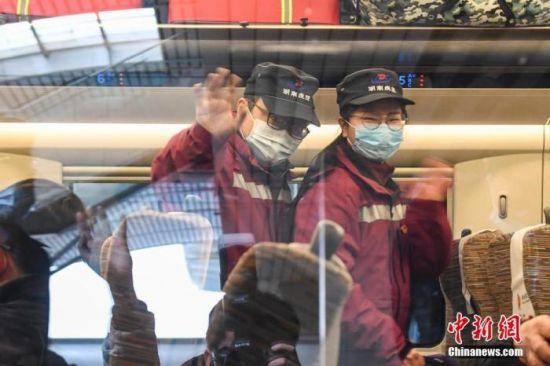 1月10日,湖南长沙,流调队员在车厢内向送行的人挥手道别。当日,湖南省流行病学调查队23名队员携带防护物资乘坐高铁前往河北省石家庄市,协助当地开展新冠肺炎疫情防控工作。 中新社记者 杨华峰 摄
