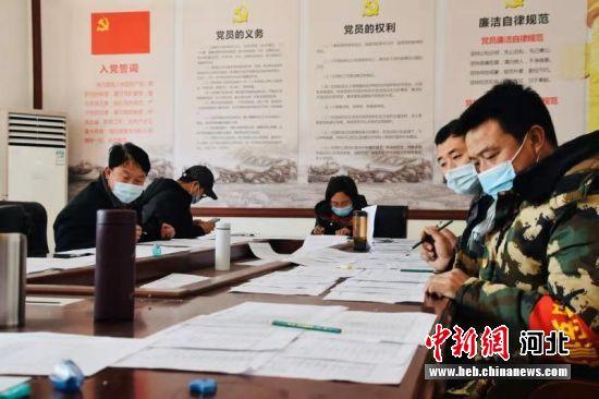 村干部在筛查核实在外务工、经商的村民信息。 贾凡 摄