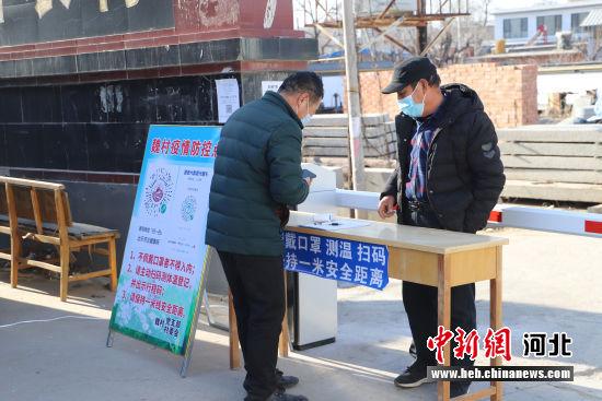 涞水镇魏村村口卡点,志愿者对出入村的人员进行信息登记。 杨猛 摄