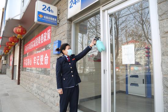 图为1月11日,妻子赵利娟在24小时自助办税服务厅外喷洒消毒液,为纳税人缴费人提供安全办税环境。 孔祥奎摄