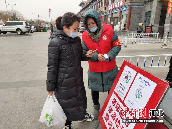 李云凤(右)正在引导出入居民扫健康码。 涞水县妇联供图