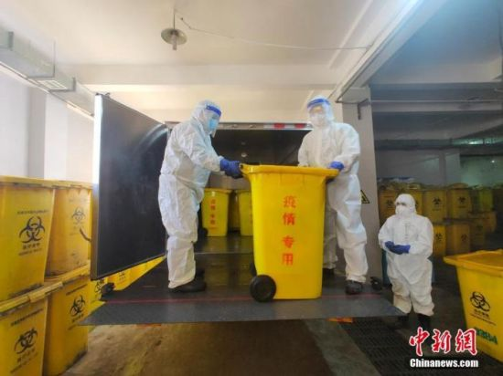 1月17日,石家庄医疗废物处置有限公司医废处置中心专用通道内,工人们在从车上搬运涉疫垃圾。 中新社记者 王天译 摄