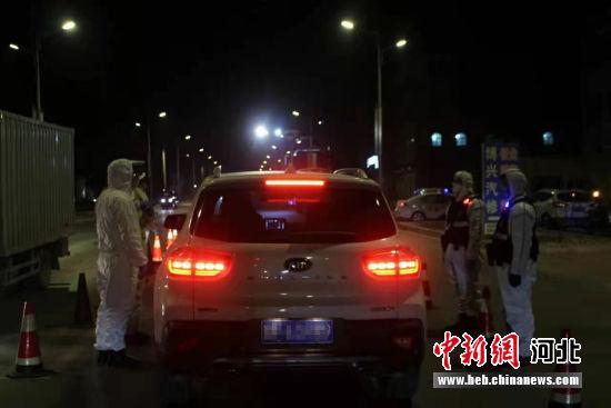 民警对出入车辆逐人测温、扫码、登记信息。 冯云 摄