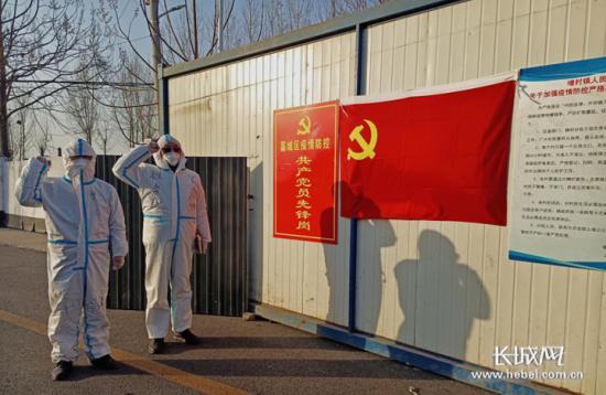 石家庄市藁城区税务局驻村疫情防控小组成员在党旗前重温入党誓词。田召飞 摄