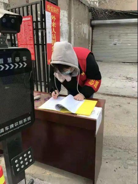图为刘悦同学对出入社区人员进行登记