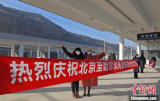 游客在庆祝京哈高铁全线贯通条幅前合影 张桂芹 摄