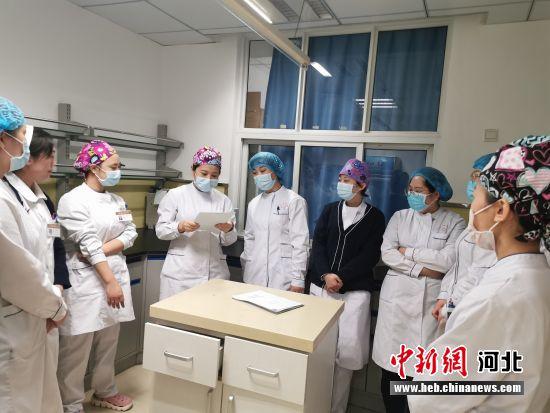 固安县总医院护士长肖永红(左五)出发去抗疫一线前与同事交接工作。 门丛硕 摄