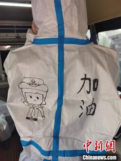 """图为母亲为高媛绘制的卡通女警与""""加油""""二字。 李洋 摄"""