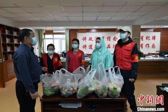 图为清真寺街社区的几名志愿者准备为小区内的独居老人送去果蔬。 翟羽佳 摄