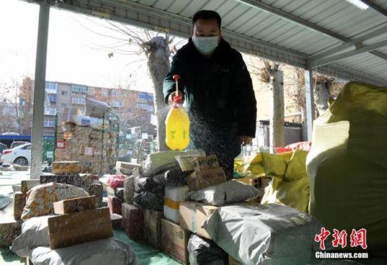 1月10日上午,石家庄市快递服务恢复运营,在中国邮政集团有限公司石家庄市分公司翟营投递部,工作人员正在对即将投递的快递进行消毒。中新社记者 陈昊 摄