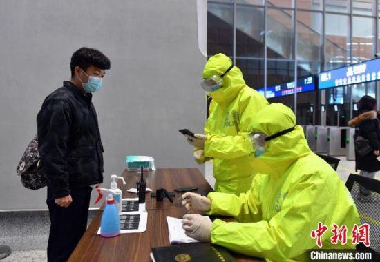 图为进入雄安站的旅客正在出示7日内核酸检测阴性证明、健康码和行程码。 韩冰 摄
