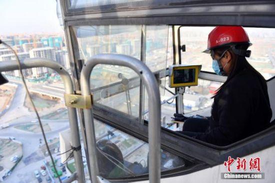 图为2月4日,黄美娇正在操作塔吊进行作业。 中新社记者 韩冰 摄