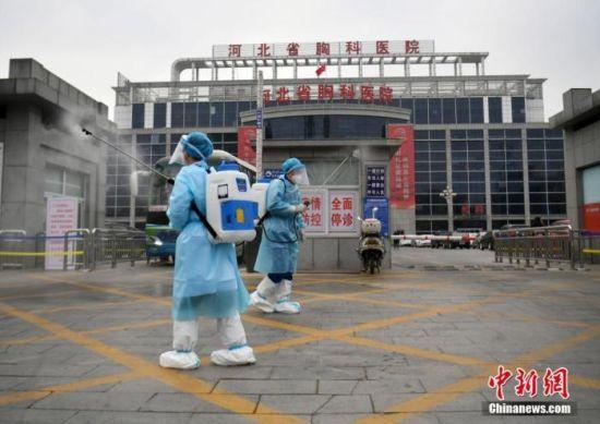 1月19日,河北石家庄,河北省胸科医院的工作人员在医院大门口消毒。 中新社记者 翟羽佳 摄
