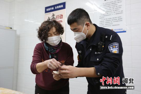 图为年轻民警向高妈妈请教包饺子。 供图