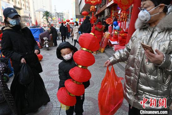 图为当日下午,石家庄南三条批发市场,小朋友开心地拿着刚买的灯笼。 中新社记者 翟羽佳 摄