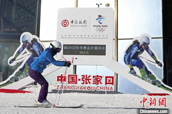 2月4日,滑雪爱好者在河北省张家口市崇礼区云顶滑雪公园冬奥会倒计时牌前滑雪。 中新社发 武殿森 摄