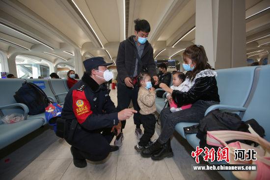 图为张少杰在候车厅提醒旅客戴好口罩。