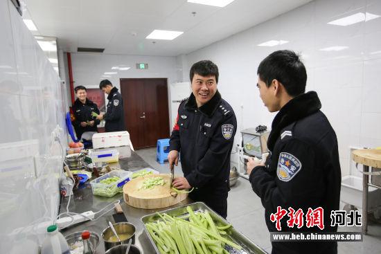 图为张少杰在食堂与同事们一起做饭。