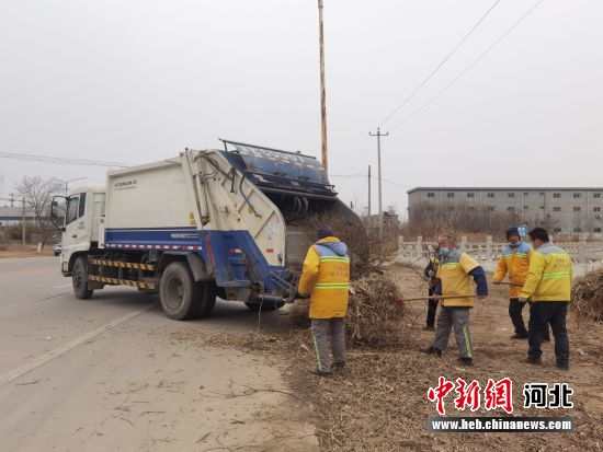 河北巨鹿县城管局工作人员正在浇水、修剪树木、打扫垃圾、清运树枝。 毕玉婷 摄
