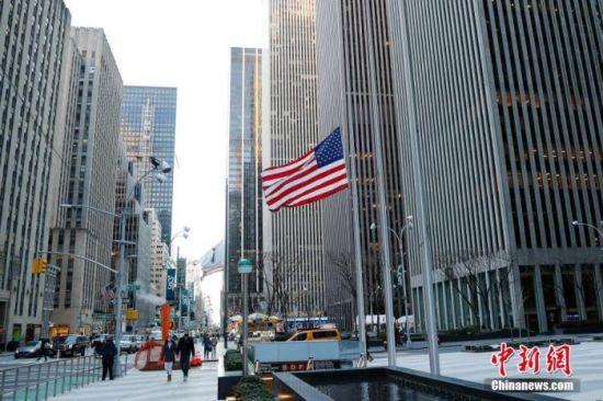 当地时间2021年2月24日,美国纽约曼哈顿街道上的美国国旗降下半旗。2月22日,美国总统拜登发布公告,下令美国境内外所有联邦建筑和军事设施降半旗,为期5天,以悼念新冠逝者。 中新社记者 廖攀 摄