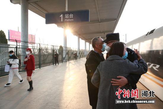 图为栗孝鑫在站台与父母拥抱。 供图