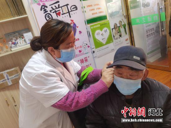 工作人员为听障人士检测听力并适配助听器。 毕玉婷 摄