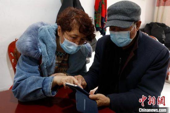 资料图:某社区工作者正在教老年人使用智能手机。杨迪 摄