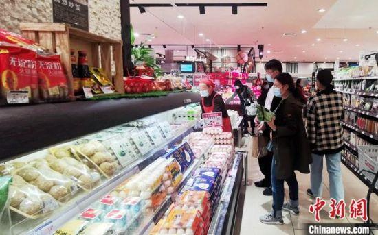 资料图:民众在一超市内选购商品。 中新社记者 刘忠俊 摄