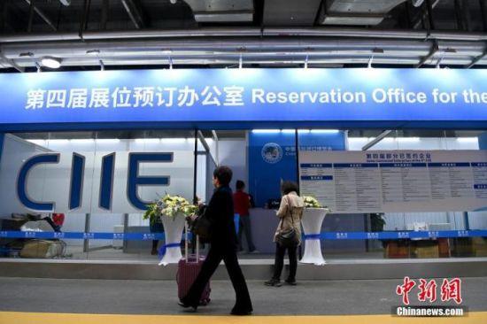 2020年11月9日,上海,第三届中国国际进口博览会的参会者经过第四届展位预订办公室。 中新社记者 侯宇 摄