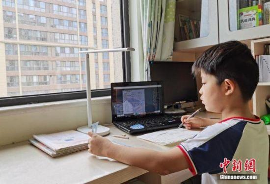 一小学生在家中通过平板电脑收看直播上数学课。(资料图片)中新社记者 翟羽佳 摄