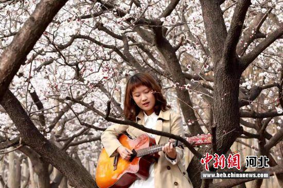 巨鹿县元泽路杏花园中一位正在弹吉他的学生。 胡良川 摄