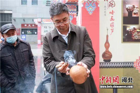 涿州非遗传承人向游客展示烙画葫芦技艺。 闫鹏 摄