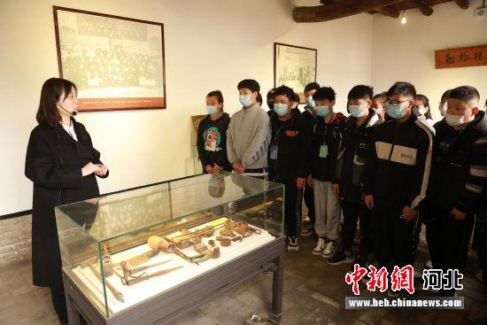 讲解员向学生讲解布里留法工艺学校(旧址)中陈列的文物。 程尚梅 摄
