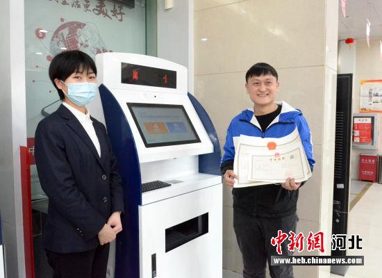 张天城(右)在白沟审批服务站办理营业执照。 李芳 摄