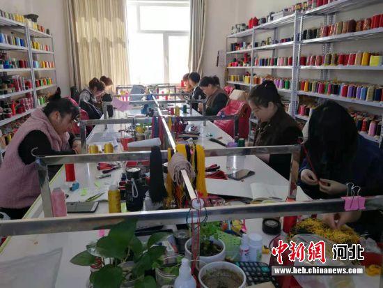 工人们正在编织手绳。 王斌 摄