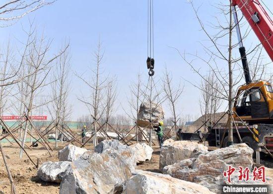 """随着京津冀协同发展的深入推进,""""未来之城""""雄安不再神秘。设立四年来,如何高标准高质量推进雄安新区建设?这个问题的答案就藏在雄安""""红、绿、蓝""""的考量之中。图为3月24日,雄安郊野公园雄安园建设工程及配套设施二标段施工现场。 中新社记者 韩冰 摄"""