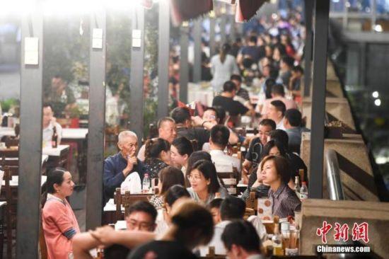 """资料图:长沙""""夜经济""""逐渐复苏。市民在夏季的夜晚出行品尝美食。 杨华峰 摄"""