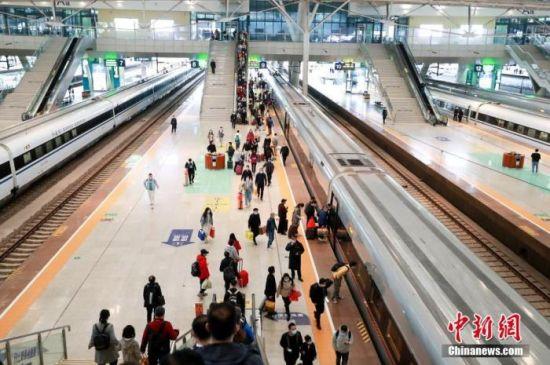 资料图:旅客在武汉火车站站台准备乘坐高铁列车。 图片来源:视觉中国