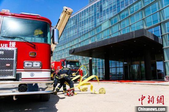 图为高层建筑灭火救援综合实战演练现场。  樊一达 摄