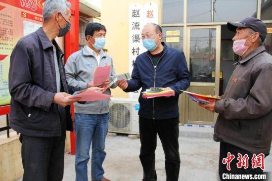 康丰民(右二)进村入户宣传发动群众种植辣椒。 姚友谅 摄